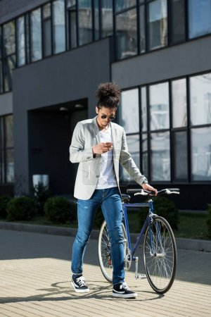 stylish young african american man using smartphone while walking with bike on street