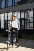 beautiful smiling blonde girl sitting on bicycle and looking away on street