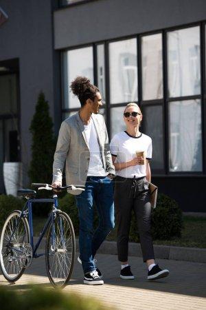 Photo pour Heureux jeune couple multiethnique regardent pendant qu'il marchait sur la rue vélo avec café pour aller - image libre de droit