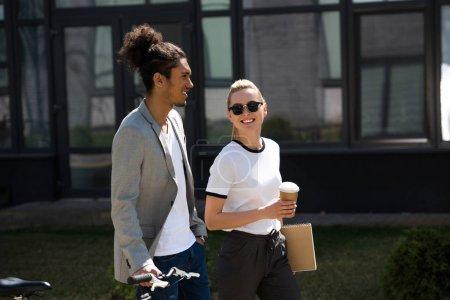 Photo pour Heureux jeune couple multiethnique parler tout en marchant sur la rue vélo avec café pour aller - image libre de droit
