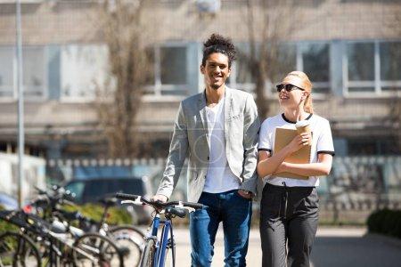 Photo pour Souriante jeune couple multiethnique marcher ensemble sur la rue vélo, café pour aller avec ordinateur portable - image libre de droit