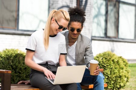 Photo pour Souriante jeune couple multiethnique à l'aide d'ordinateur portable et de boire du café pour aller assis ensemble sur banc - image libre de droit