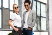portrait of beautiful stylish multiethnic couple in sunglasses standing with hands in pockets and smiling at camera
