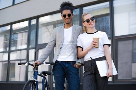 cheerful young multiethnic couple standing with laptop, coffee to go and bicycle on street