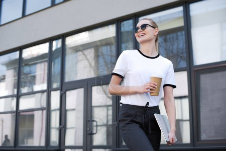 beautiful smiling blonde girl with coffee to go and laptop walking and looking away on street