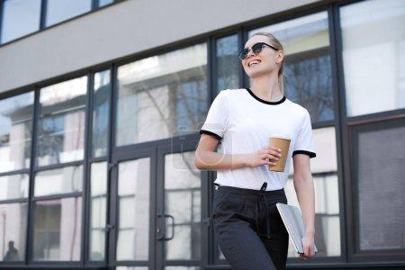 Photo pour Belle fille blonde souriante avec café pour aller et ordinateur portable à pied et à la recherche de loin sur la rue - image libre de droit