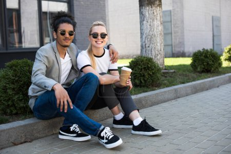 happy young multiethnic couple smiling at camera while sitting on street with coffee to go