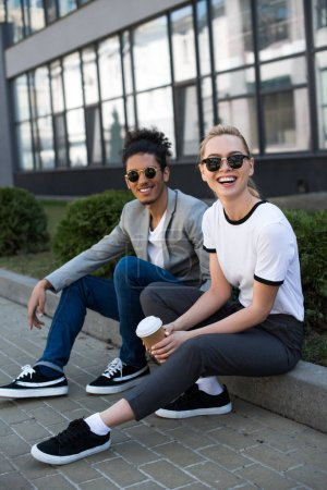 Photo for Cheerful young multiethnic couple in sunglasses smiling at camera while drinking coffee to go on street - Royalty Free Image