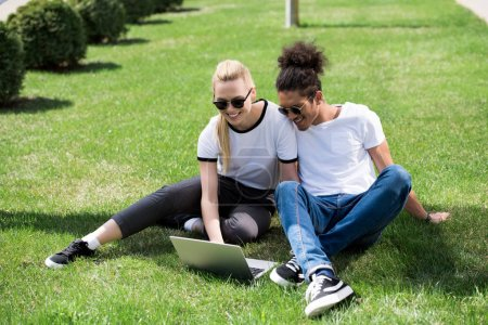 happy young multiethnic couple sitting on grass and using laptop
