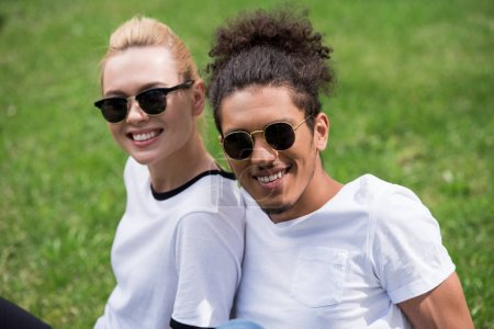 portrait of beautiful young multiethnic couple in sunglasses sitting together on grass and smiling at camera