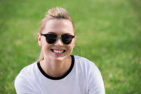 Photo for Portrait of beautiful young blonde woman in sunglasses smiling at camera outdoors - Royalty Free Image