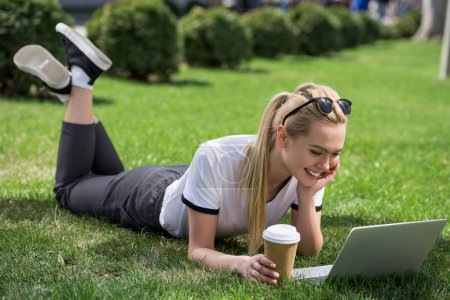 beautiful smiling girl with coffee to go lying on green grass and using laptop