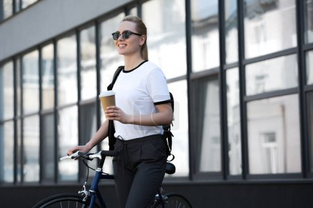 beautiful smiling blonde girl holding paper cup and standing with bicycle on street
