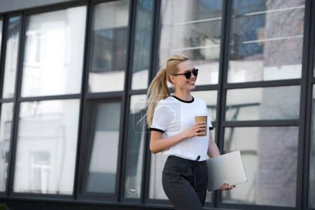 Foto de Hermosa muchacha sonriente en gafas de sol sosteniendo la taza de papel y ordenador portátil mientras camina fuera del edificio - Imagen libre de derechos