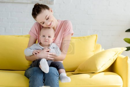 young mother hugging her little son while sitting on sofa