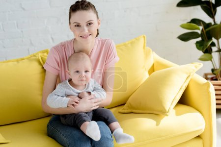young smiling mother with little son sitting on sofa