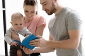happy family with baby boy dearing book together