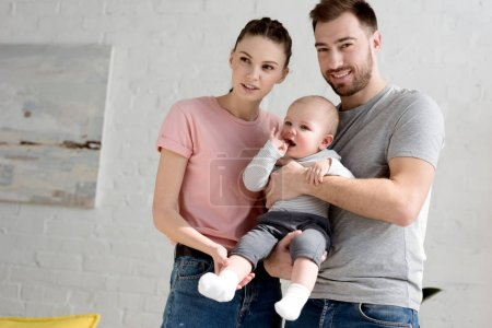 young happy parents with little baby boy at home