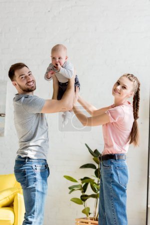 happy parents playing with little son at home