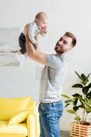 young daddy playing with little son at home