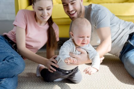 happy parents playing with baby boy sitting on floor