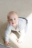 adorable smiling little boy crawling on floor