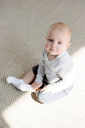 adorable little baby boy sitting on floor