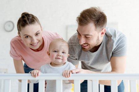 Photo pour Heureux parents avec bébé garçon en lit de bébé à la maison - image libre de droit