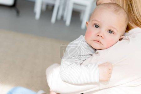 infant son lying on mothers hands