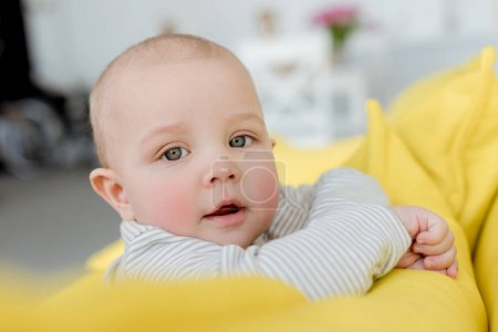 adorable little baby boy on yellow sofa looking at camera