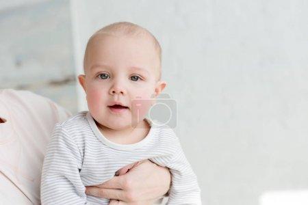 petit fils heureux sur les mains de mères regardant la caméra
