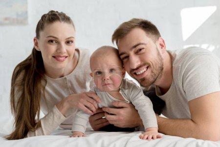 parents souriants avec petit garçon sur le lit