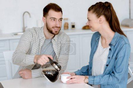 boyfriend pouring coffee for girlfriend in kitchen