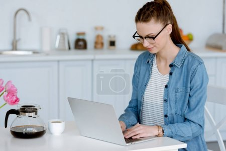 Photo for Young female freelancer using laptop on kitchen with coffee - Royalty Free Image
