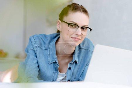 Photo pour Belle jeune femme à lunettes à l'aide d'ordinateur portable - image libre de droit