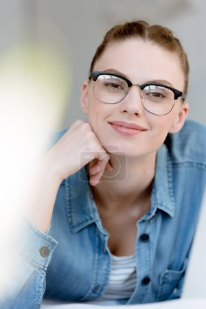 portrait of beautiful young woman in eyeglasses looking at camera