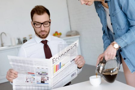 businessman in eyeglasses reading economics newspaper while wife pouring coffee in cup on kitchen