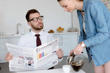 businessman with economics newspaper looking at wife pouring coffee in cup for breakfast