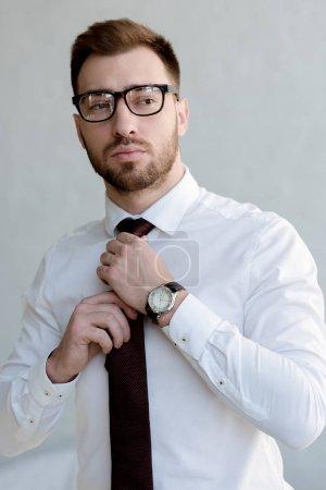 Photo pour Homme d'affaires confiant en cravate et lunettes posant près du mur blanc - image libre de droit