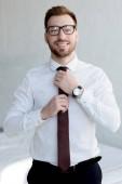 stylish businessman in tie posing near white wall