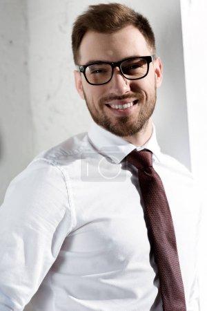 Photo pour Homme d'affaires souriant à lunettes, regardant la caméra - image libre de droit