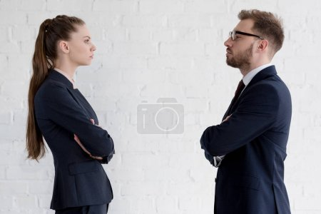 serious businesspeople with crossed arms looking at each other