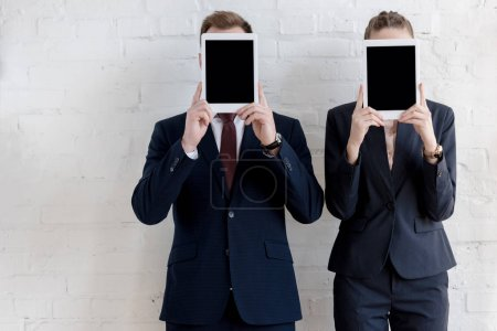 businesspeople in formal wear holding digital tablets with blank screens