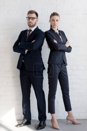 professional business team in suits posing with crossed arms near white wall