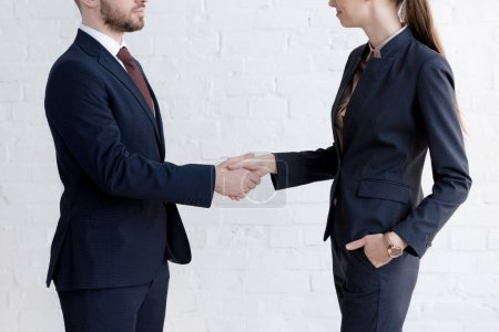 Photo for Cropped view of businesspeople shaking hands near white wall - Royalty Free Image