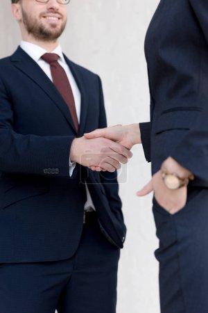 Photo pour Vue recadrée de collègues d'affaires en costume se serrant la main - image libre de droit