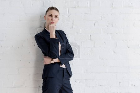 beautiful thoughtful businesswoman in suit posing near white wall
