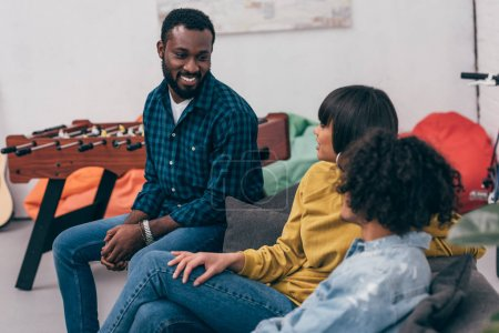 group of multicultural smiling friends sitting on couch and talking to each other