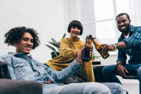 smiling multicultural young friends clinking bottles of beer