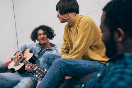 young mixed race man playing on acoustic guitar to multiethnic friends